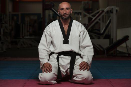 Black Belt Karate Man Sit On A Position To Start Or Finish Practicing