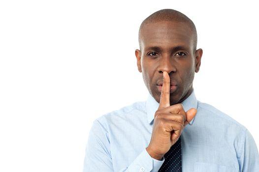 Businessman shows silence gesture