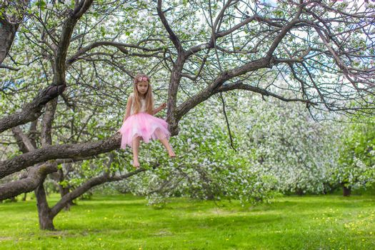 Little adorable girl on blossoming apple tree
