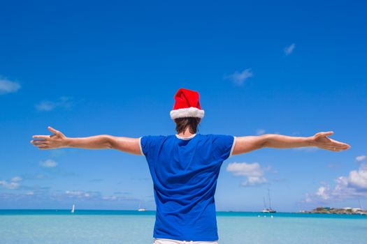 Back view of young man in santa hat on tropical beach