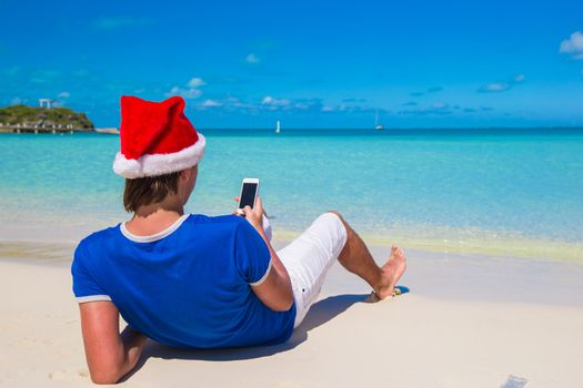 Back view of young man in santa hat with phone on tropical caribbean beach