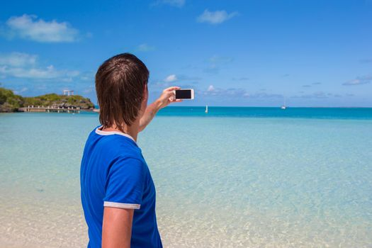 Young man in santa hat with phone on tropical caribbean beach