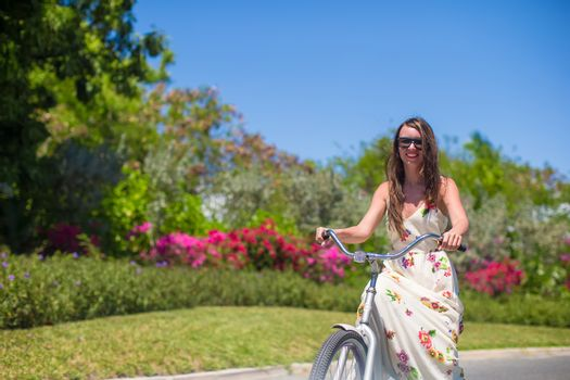 Young woman on vacation biking at lush garden