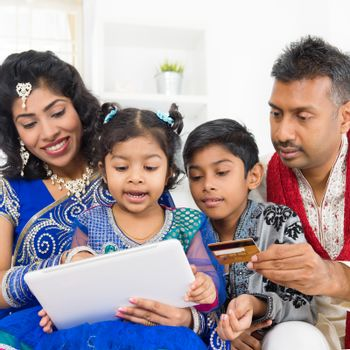 Indian Asian family using digital tablet pc computer online shopping with credit card at home. India family living lifestyle. Happy smiling parents and children.