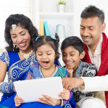 Indian family using digital computer tablet at home. Asian family living lifestyle.