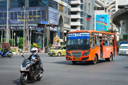 BANGKOK, THAILAND - 21 NOV 2013: Public transport bus and motorbike pass crossroads street with modern buildings on background