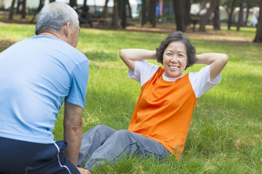 smiling senior grandmother doing sit-ups in the park