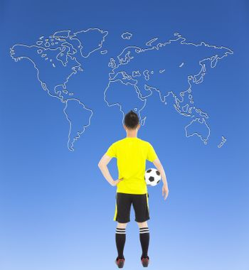 soccer player holding a soccer and looking global map