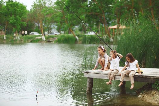 Tree children fishing in pond in summer