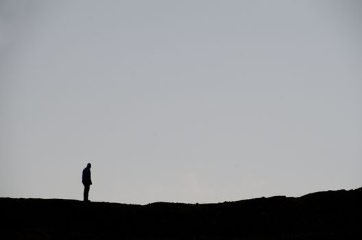 man and mountain in black with gray background