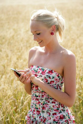 Young attractive woman standing in a wheat field, using her cellphone. She looks happy and relaxed.
