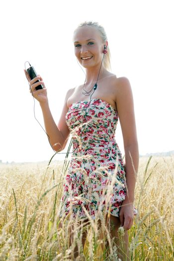 Young attractive woman is standing in a wheat field and listening to music with her smartphone. She looks happy and relaxed.