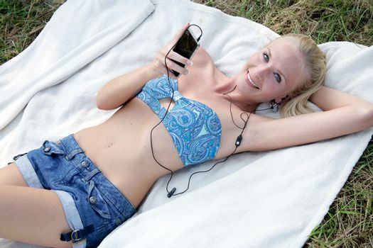 Young woman is lying on a blanket and listen to music