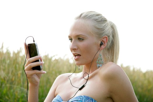 Young woman is sitting in the open countryside and listen to music