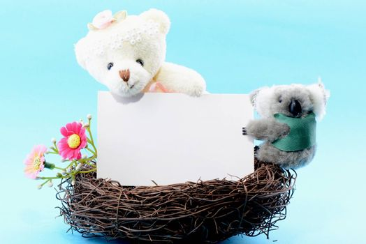 Nest with a blank white card held by a toy teddy bear and koala on a blue background