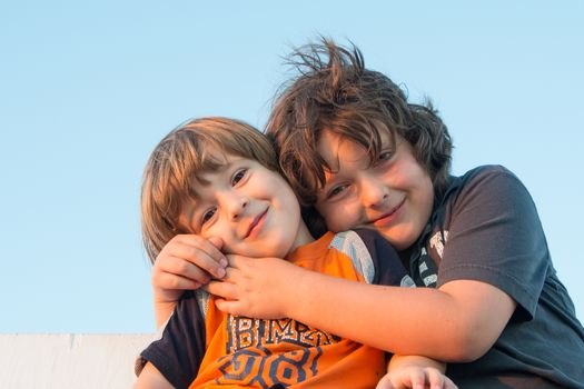 Brothers hugging at sunset