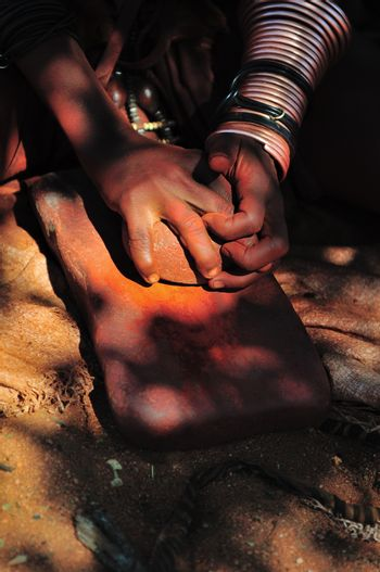 Himba woman grinding red ochre with a stone on another stone