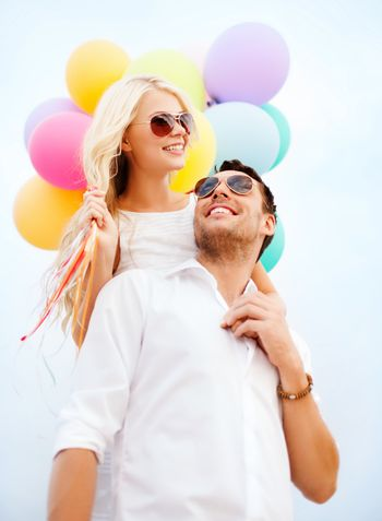 summer holidays, celebration and dating concept - couple with colorful balloons