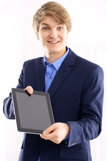 Portrait of a young elegant man in blue suit holding a digital tablet