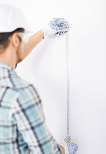 architect measuring wall with flexible ruler