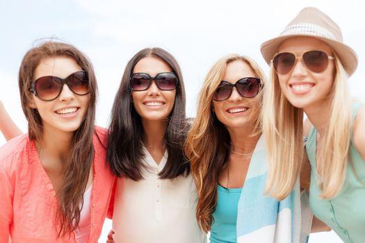 girls in shades having fun on the beach