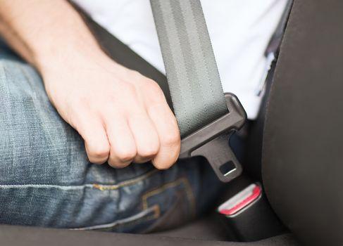 man fastening seat belt in car