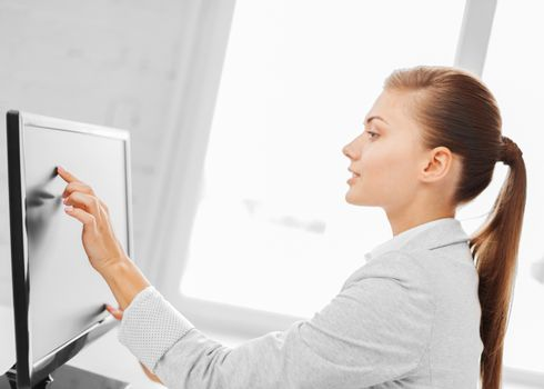 smiling businesswoman with touchscreen in office