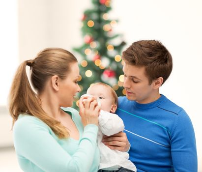 christmas, x-mas, winter, family, people, happiness concept - happy family and adorable baby with feeding-bottle