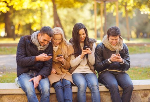summer, holidays, vacation, happy people concept - group of friends or couples with smartphones having fun in autumn park