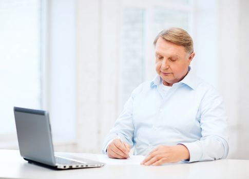 old man filling a form at home