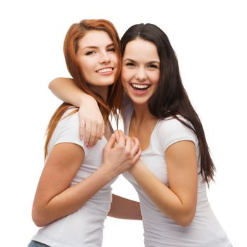 friendship and happy people concept - two laughing girls in white t-shirt hugging