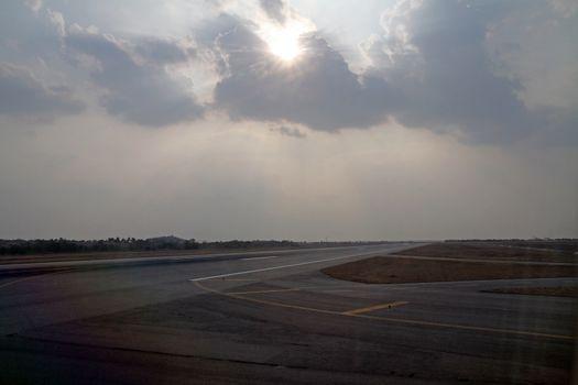 Sun Burst Cloudy Sky over airport runway