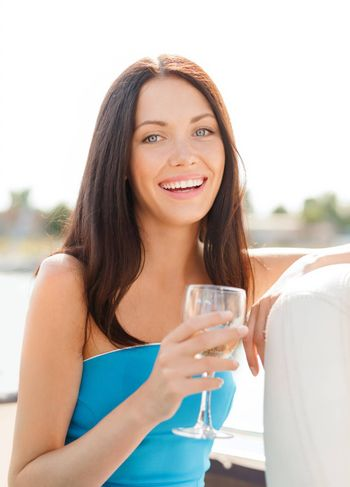 summer holidays, vacation and celebration concept - laughing girl with champagne glass