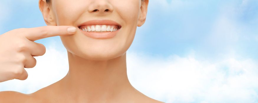 beauty and dental health concept - closeup picture of beautiful woman pointing finger to her teeth