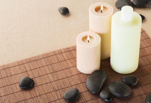 shampoo bottle, massage stones and candles