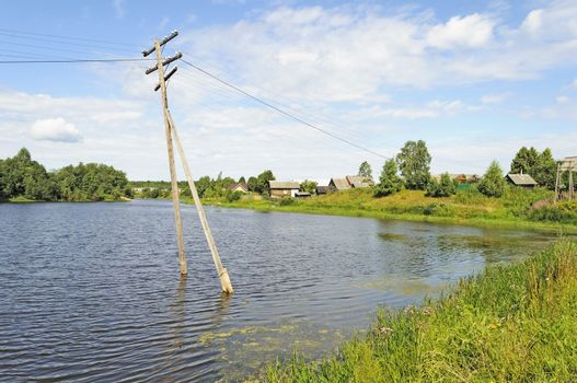 Electric pole in water during a river flood. Country landscape
