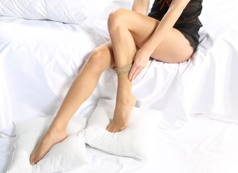 Putting stockings on sexy legs
