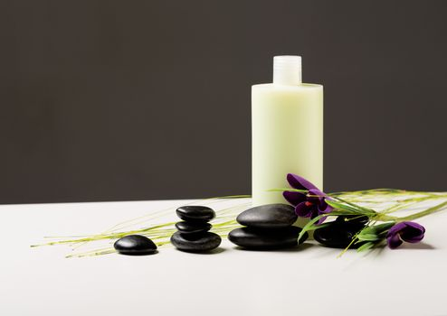 shampoo bottle, massage stones and iris flower