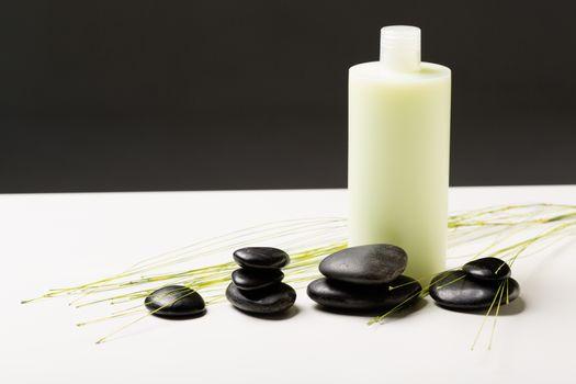 shampoo bottle, massage stones and green plant