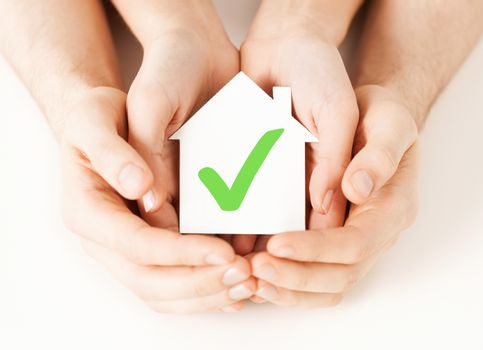hands holding house with check mark