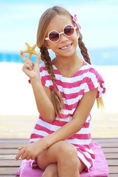Child holding seashell on the summer beach