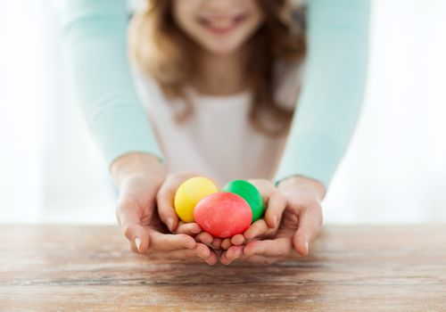 easter, family, holiday and child concept - close up of little girl and mother holding colored eggs