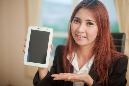 Asian business woman presenting a tablet and smiling to the camera