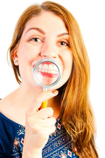 girl with magnifier showing his beautiful white teeth