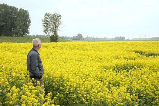 man stading in the middel of rapeseed flower field
