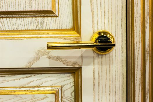 gilded handle on the beige interior door