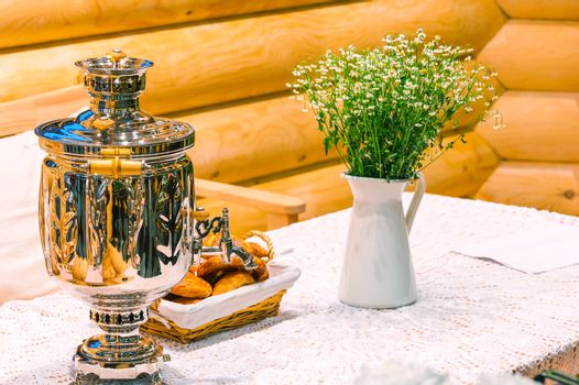 shiny samovar and bouquet of flowers on a rustic table