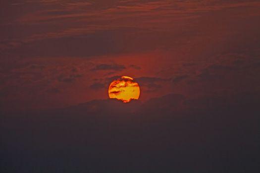 Orange Orb of Sun behind clouds dramatic sunset