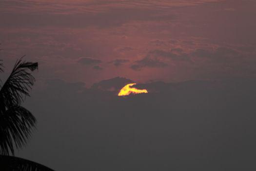 Orange  Sun hidden by  clouds dramatic sunset