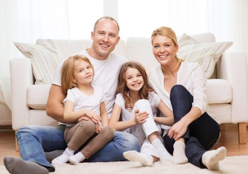 parents and two girls sitting on floor at home
